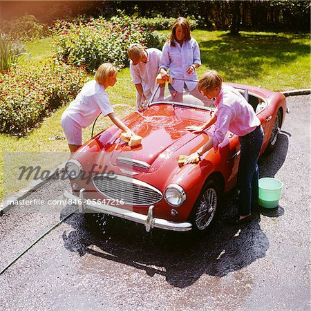 1970s FOUR TEENAGERS WASHING RED AUSTIN HEALEY SPORTS CONVERTIBLE AUTOMOBILE MAN WOMAN OVERHEAD OUTDOOR Stock Photo - Rights-Managed, Image code: 846-05647216