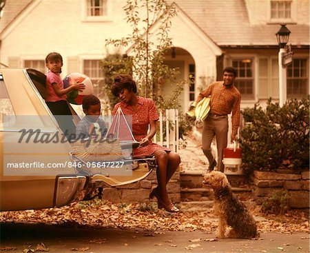 1970s AFRICAN-AMERICAN FAMILY LOADING STATION WAGON PICNIC DOG MOTHER FATHER BOY GIRL SUBURBAN   HOUSE Stock Photo - Rights-Managed, Image code: 846-05647227
