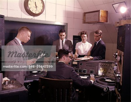 1960s GROUP OF 5 PEOPLE IN RADIO STATION CONTROL ROOM DISK JOCKEY DJ TURNTABLES BROADCASTING MEDIA COMMUNICATIONS