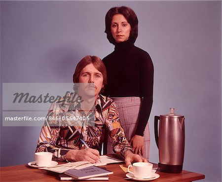 1970s SERIOUS COUPLE HUSBAND SITTING WEARING LOUD PRINT SHIRT WRITING FAMILY BUDGET WIFE STANDING BEHIND COFFEE POT ON DESK Stock Photo - Rights-Managed, Image code: 846-05647405