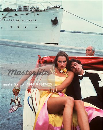 1970s - 1980s COUPLE IN OPEN HANSOM CAB MAN TUXEDO ASLEEP WOMAN ANGRY ON DOCK CRUISE SHIP BYSTANDER Stock Photo - Rights-Managed, Image code: 846-05647425