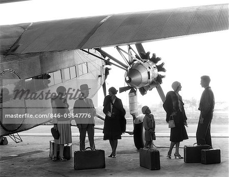 1920s - 1930s GROUP OF PASSENGERS STANDING UNDER WING OF FORD TRI-MOTOR AIRPLANE WITH BAGGAGE