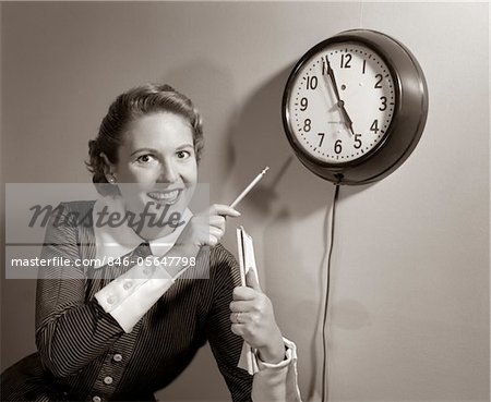 1950s SMILING WOMAN STENOGRAPHER OFFICE WORKER HOLDING STENO PAD POINTING WITH PENCIL TO CLOCK 5 MINUTES TILL QUITTING TIME Stock Photo - Rights-Managed, Image code: 846-05647798
