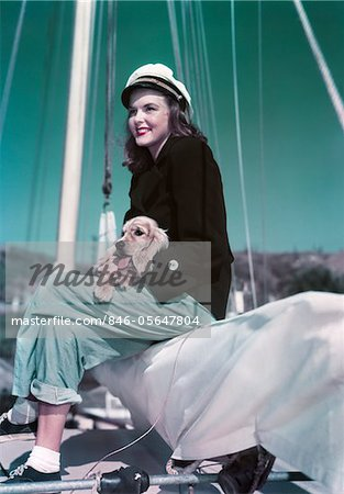 1940s - 1950s SMILING WOMAN WEARING SAILING YACHTING OUTFIT SITTING ON EDGE OF SAILBOAT HOLDING PUPPY IN LAP Stock Photo - Rights-Managed, Image code: 846-05647804