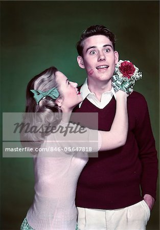 1940s - 1950s TEEN COUPLE GIRL HOLDING NOSEGAY BOUQUET HUGGING SURPRISED BOY LIPSTICK KISS ON CHEEK Stock Photo - Rights-Managed, Image code: 846-05647818