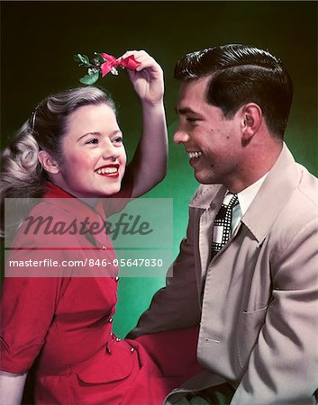 1950s SMILING TEEN COUPLE GIRL HOLDING CHRISTMAS MISTLETOE OVER HEAD Stock Photo - Rights-Managed, Image code: 846-05647830