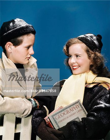 1940s TEEN COUPLE WEARING WINTER HATS GLOVES COATS GIRL SMILING CARRYING SCHOOL BOOKS Stock Photo - Rights-Managed, Image code: 846-05647858