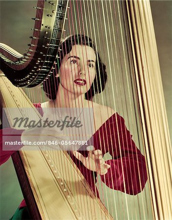 1940s - 1950s WOMAN PLAYING HARP WEARING RED VELVET GOWN Stock Photo - Rights-Managed, Image code: 846-05647881