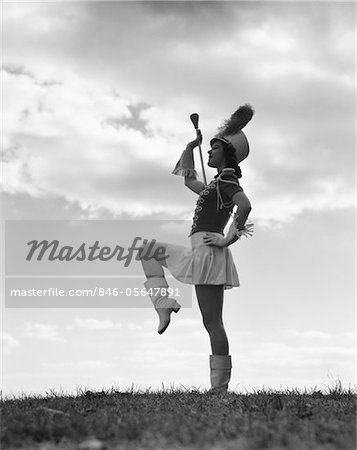 1940s SILHOUETTE OF MAJORETTE AGAINST SKY AND CLOUDS