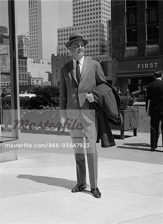 1950s - 1960s BUSINESSMAN WEARING SUIT HAT CARRYING TOP COAT STANDING ON CITY STREET