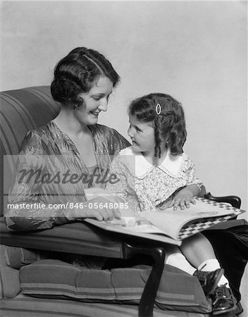 1920s - 1930s MOTHER & DAUGHTER SMILING SITTING IN CHAIR READING BOOK Stock Photo - Rights-Managed, Image code: 846-05648085