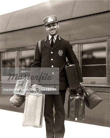 1930s - 1940s PORTRAIT SMILING AFRICAN AMERICAN MAN RED CAP PORTER CARRYING LUGGAGE BAGS SUITCASES PASSENGER RAILROAD TRAIN Stock Photo - Rights-Managed, Image code: 846-05648087