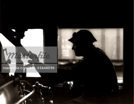 1920s - 1930s - 1940s SILHOUETTE TRAIN ENGINEER AT CONTROLS IN LOCOMOTIVE CAB OF RAILROAD STEAM ENGINE Stock Photo - Rights-Managed, Image code: 846-05648090