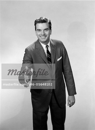1960s SMILING SALESMAN OR BUSINESSMAN LEANING FORWARD EXTENDING HAND FOR HANDSHAKE Stock Photo - Rights-Managed, Image code: 846-05648102