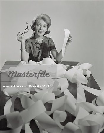 1960s WOMAN HOLDING EYEGLASSES AND END OF EXTREMELY LONG TAPE FROM OFFICE MACHINE Stock Photo - Rights-Managed, Image code: 846-05648160
