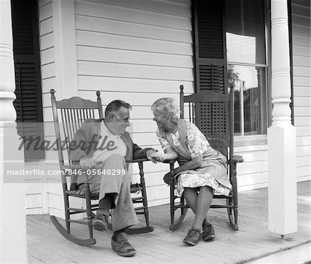 Astounding 1970S Elderly Couple In Rocking Chairs On Porch Holding Bralicious Painted Fabric Chair Ideas Braliciousco