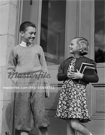 1940s SMILING BOY & GIRL HOLDING SCHOOL BOOKS BY DOORS Stock Photo - Rights-Managed, Image code: 846-05648351