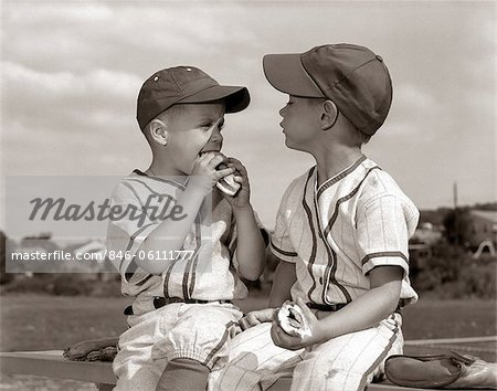 1960s LITTLE LEAGUE BASEBALL BOYS IN CAPS AND UNIFORMS EATING HOT DOGS Stock Photo - Rights-Managed, Image code: 846-06111777