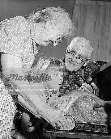 1950s 1960s EXCITED LITTLE GIRL GRANDDAUGHTER WITH GRANDPARENTS WATCHING ROAST TURKEY COMING OUT OF OVEN Stock Photo - Rights-Managed, Image code: 846-06111801