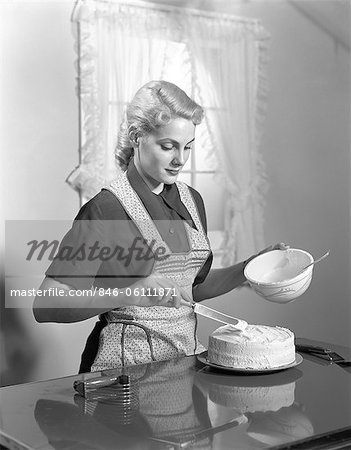 1940s WOMAN IN KITCHEN WEARING APRON FROSTING CAKE INDOOR