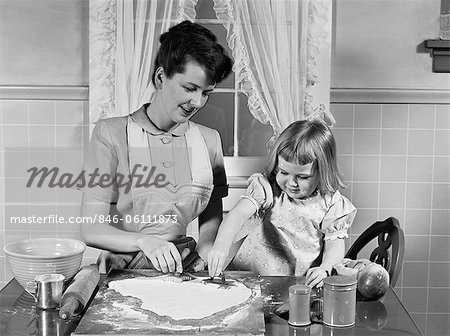 1950s MOTHER & DAUGHTER BAKING TOGETHER IN KITCHEN CUTTING DOUGH WITH COOKIE CUTTERS