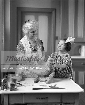 1920s LITTLE GIRL HELPING GRANDMOTHER STUFF TURKEY