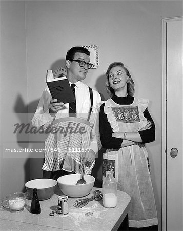 1950s COUPLE IN KITCHEN WITH HUSBAND LEARNING TO COOK WHILE WIFE WATCHES