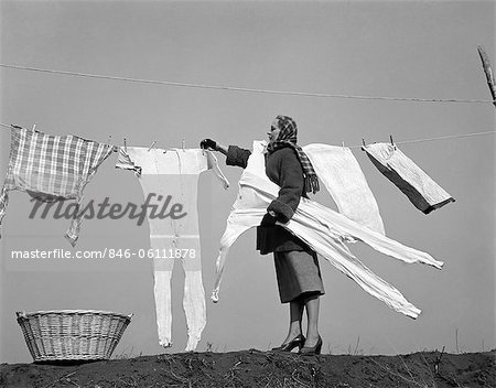 1950s HOUSEWIFE REMOVING FROZEN LONG JOHNS FROM CLOTHESLINE Stock Photo - Rights-Managed, Image code: 846-06111878