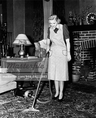 1930s 1940s WOMAN HOUSEWIFE WEARING APRON PUSHING ELECTRIC VACUUM CLEANER IN ORNATE LIVING ROOM HOUSE CHORE Stock Photo - Rights-Managed, Image code: 846-06111883