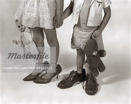 1950s 1960s CLOSE-UP OF LITTLE GIRL & BOY FROM NECK DOWN WEARING PARENTS' SHOES Stock Photo - Rights-Managed, Image code: 846-06111921