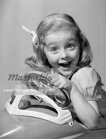 1950s PORTRAIT OF LITTLE GIRL DRIVING TOY CAR WITH EXCITED EXPRESSION LOOKING AT CAMERA Stock Photo - Rights-Managed, Image code: 846-06111959