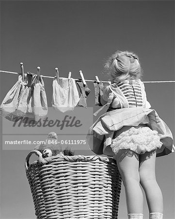 1950s BACK VIEW OF GIRL HANGING LAUNDRY WIND BLOWING SKIRT TO SHOW RUFFLED PANTIES Stock Photo - Rights-Managed, Image code: 846-06111975