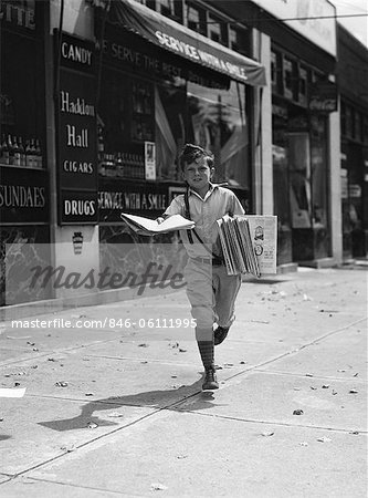 1930s NEWSPAPER BOY IN KNICKERS WALKING TOWARDS CAMERA ON STREET HOLDING PHILADELPHIA INQUIRER Stock Photo - Rights-Managed, Image code: 846-06111995