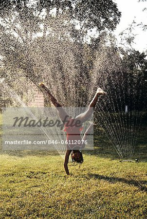 LITTLE GIRL CARTWHEELING THROUGH LAWN SPRINKLER Stock Photo - Rights-Managed, Image code: 846-06112076