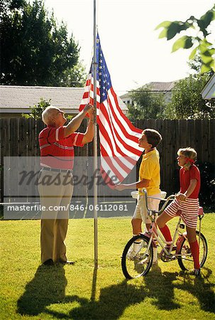 GRANDFATHER RAISING FLAG ON POLE TWO GRANDCHILDREN WATCHING Stock Photo - Rights-Managed, Image code: 846-06112081