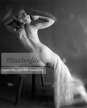 1960s BACK VIEW OF NUDE BLONDE WITH SHEER CLOTH DRAPED OVER LEGS SITTING ON STOOL LEANING TO SIDE STRETCHING OUT ARMS Stock Photo - Rights-Managed, Image code: 846-06112209