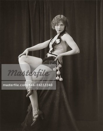 1920s SIDE VIEW OF FLAPPER WOMAN IN VELVET HOT PANTS & SEQUINED VEST SITTING ON PEDESTAL WITH LEGS CROSSED LOOKING TOWARD CAMERA Stock Photo - Rights-Managed, Image code: 846-06112240