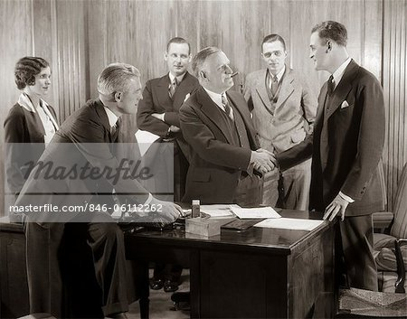 1930s GROUP BUSINESS MEN AND WOMAN IN OFFICE BOSS SHAKING HANDS WITH NEW HIRE