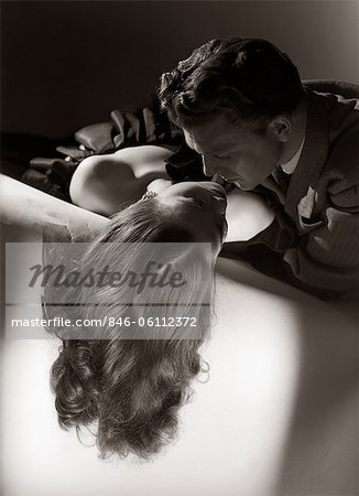 1940s 1950s ROMANTIC COUPLE EMBRACING ABOUT TO KISS ON SOFA Stock Photo - Rights-Managed, Image code: 846-06112372
