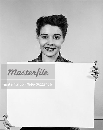 1950s WOMAN HOLDING BLANK SIGN IN FRONT OF CHEST SMILING INDOOR