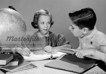 1960s BOY AND GIRL DOING HOMEWORK TOGETHER GLOBE AND BOOKS ON TABLE STUDIO INDOOR Stock Photo - Rights-Managed, Image code: 846-06112421