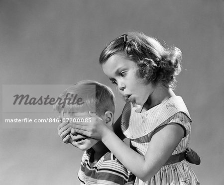1950s 1960s GUESS WHO GIRL HOLDS HER HANDS OVER BOYS EYES BLIND GAME TEASING PLAYING BOY GIRLS Stock Photo - Rights-Managed, Image code: 846-07200085