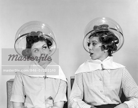 1960s TWO WOMEN SITTING UNDER SALON HAIRDRYERS GOSSIPING TALKING Stock Photo - Rights-Managed, Image code: 846-07200140