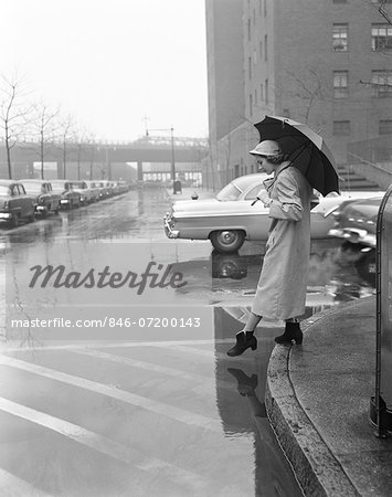 1950s WOMAN IN RAIN COAT HAT BOOTS HOLDING  UMBRELLA CROSSING CITY STREET IN WET FOUL WEATHER Stock Photo - Rights-Managed, Image code: 846-07200143