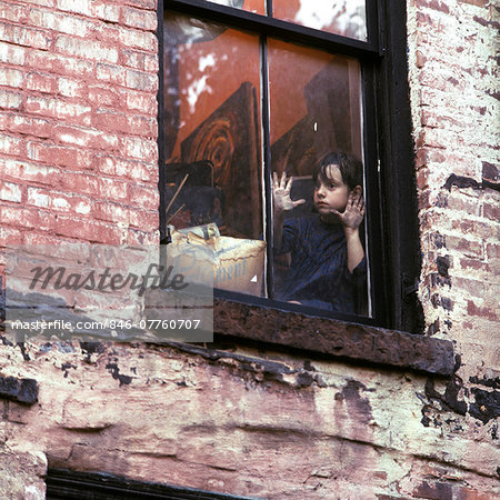 1960s 1970s SINGLE SAD LITTLE GIRL SITTING IN WINDOW OF WORN URBAN BRICK BUILDING Stock Photo - Rights-Managed, Image code: 846-07760707