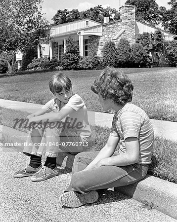 1970s TWO EARLY TEENAGE BOYS SITTING ON CURB SUBURBAN NEIGHBORHOOD TALKING Stock Photo - Rights-Managed, Image code: 846-07760713