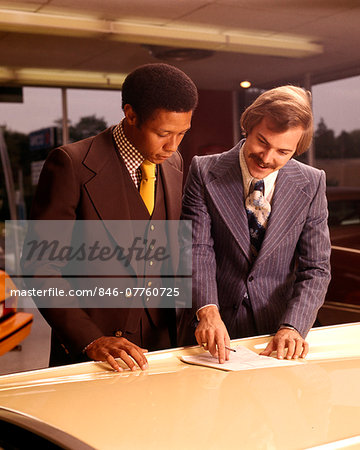 1970s TWO MEN CUSTOMER AND SALESMAN READING SALES CONTRACT ON HOOD OF NEW CAR IN DEALERSHIP SALES SHOWROOM Stock Photo - Rights-Managed, Image code: 846-07760725