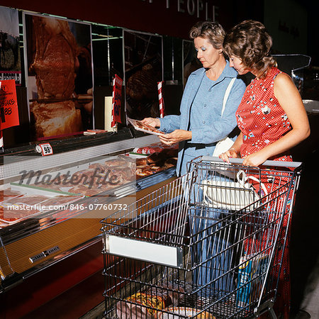 1970s TWO WOMEN MOTHER AND DAUGHTER PUSHING A SHOPPING CART IN MEAT DEPARTMENT OF SUPERMARKET Stock Photo - Rights-Managed, Image code: 846-07760732