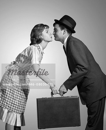 1950s 1960s HOMEMAKER WIFE IN CHECKED APRON KISSING BUSINESSMAN HUSBAND IN SUIT HAT AND TIE AS SHE HANDS HIM A BRIEFCASE