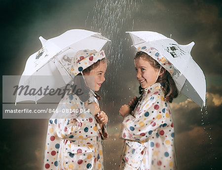 1960s SMILING TWIN GIRLS WEARING MATCHING POLKA DOT RAIN COATS AND HATS STANDING UNDER UMBRELLAS IN THE RAIN Stock Photo - Rights-Managed, Image code: 846-08140064